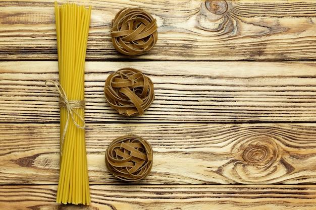 Sammlung der draufsicht der italienischen teigwaren über hölzernen hintergrund der weinlese. Premium Fotos