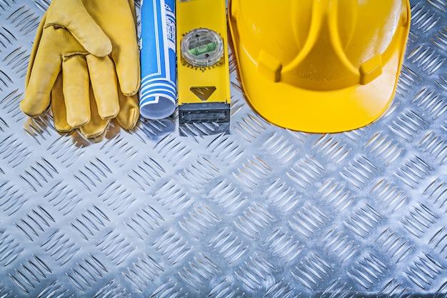 Sammlung von blau gerollten blaupausen, die helm-sicherheitshandschuhe-konstruktionsniveau auf wellblechhintergrund bauen Premium Fotos