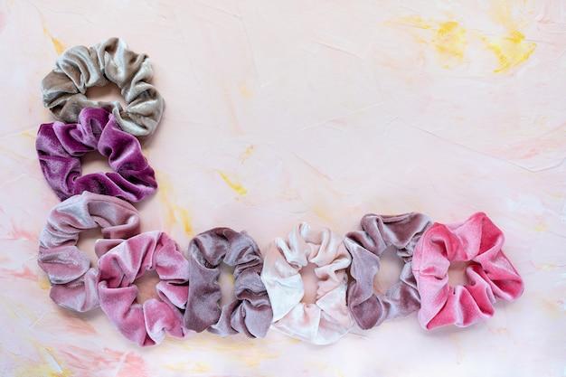 Sammlung von trendigen samt-haargummis auf rosa hintergrund. Premium Fotos