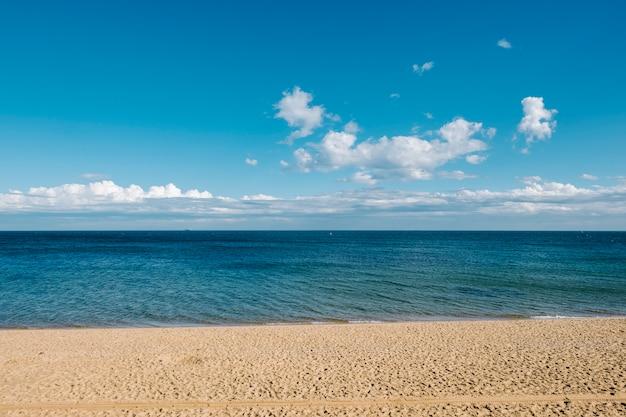 Sand und meer und hintergrund des blauen himmels Kostenlose Fotos