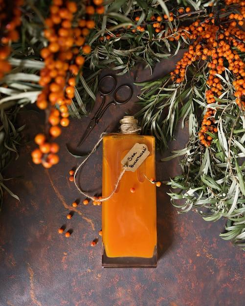 Sanddornsirup in der glasweinleseflasche und in den brunchs des sanddorns Premium Fotos