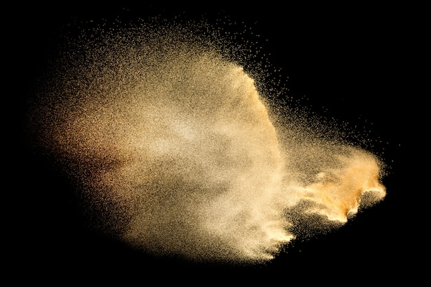 Sandexplosion lokalisiert auf schwarzem. frieren sie bewegung des sandigen staubspritzens ein. Premium Fotos