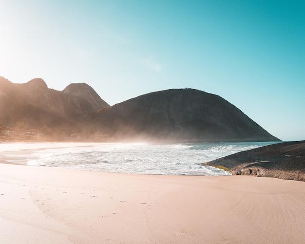 Sandküste eines schönen meeres mit klarem blauem himmel und sonnenlicht Kostenlose Fotos