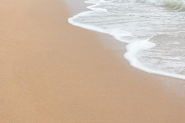 Sandstrand mit welle des wassers Premium Fotos