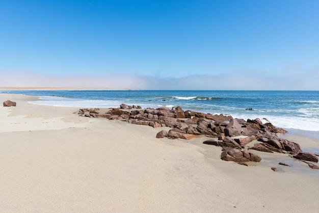 Sandstrand und küste am atlantik bei cape cross, namibia, berühmt für die nahe gelegene robbenkolonie. klarer blauer himmel. Premium Fotos