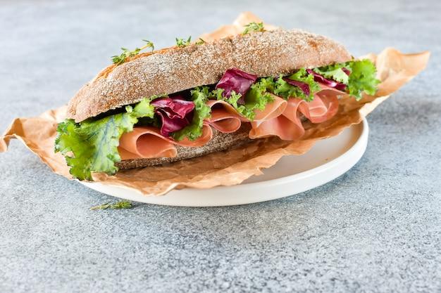 Sandwich aus getreide baguette schinken, salat, grünkohl auf einem grauen hintergrund Premium Fotos