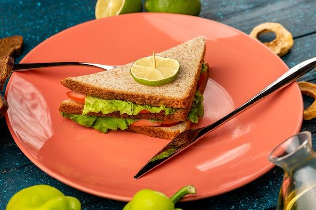 Sandwich innenplatte zusammen mit grünem paprika und zitrone auf blau Kostenlose Fotos