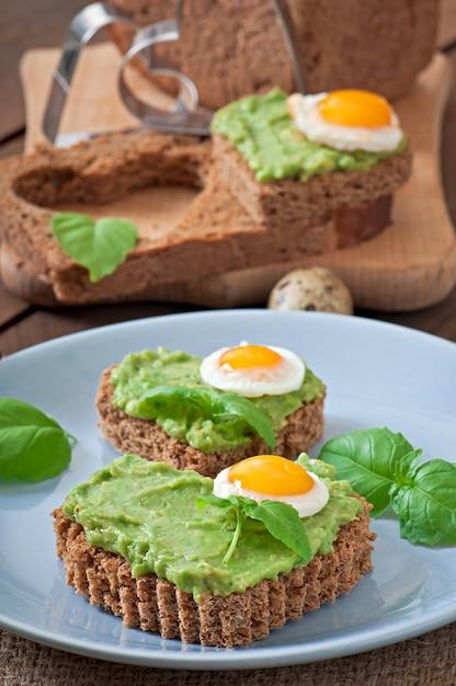 Sandwich mit avocadopaste und ei in form des herzens Premium Fotos