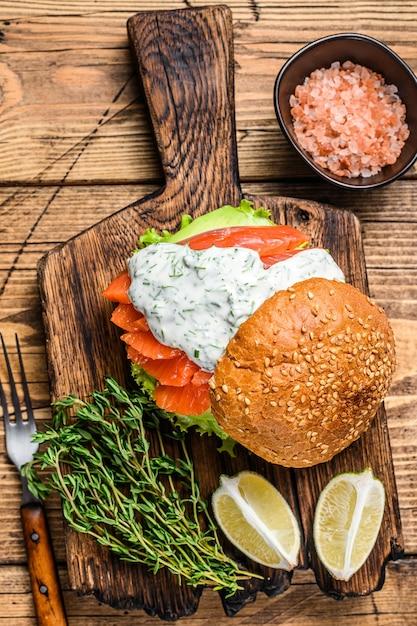 Sandwich mit gesalzenem fischlachs, avocado, burgerbrötchen, senfsauce und eisbergsalat Premium Fotos