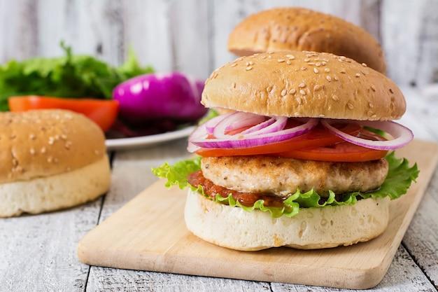 Sandwich mit hühnchenburger, tomaten, roten zwiebeln und salat Kostenlose Fotos