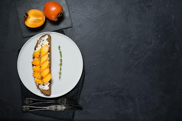 Sandwich mit persimone und weichkäse mit copyspace. Premium Fotos