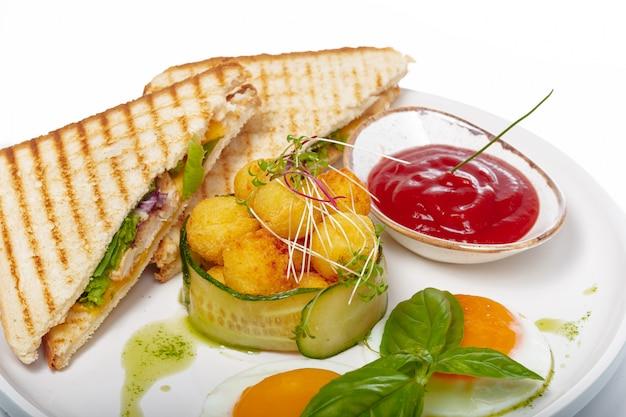 Sandwich mit schinken, käse, tomaten, salat und geröstetem brot. draufsicht isoliert. Premium Fotos