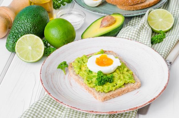 Sandwich mit vollkornbrot, zerdrückter avocado und gekochten eiern auf der platte. Premium Fotos