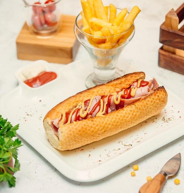 Sandwich mit wurst mit sauce und pommes Kostenlose Fotos