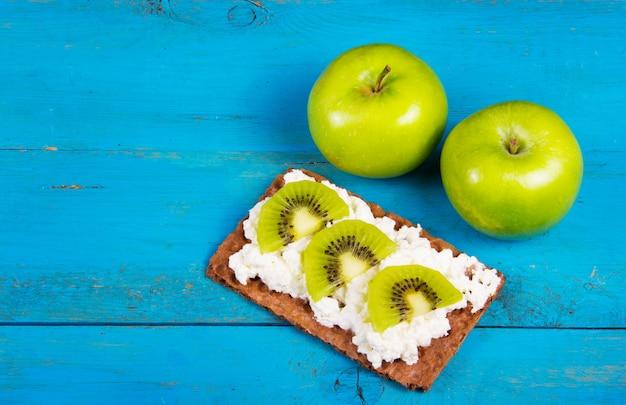 Sandwich mit zwei grünen äpfeln und gesundem getreide mit frischkäse und kiwischeiben. ein nützliches hausgemachtes frühstück. vegetarisches essen. gesundes und leckeres essen. speicherplatz kopieren. Premium Fotos