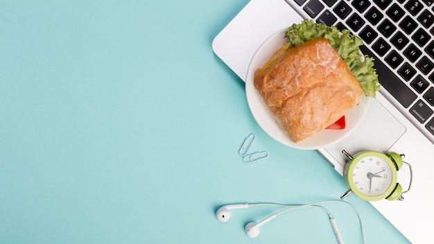 Sandwich, wecker, kopfhörer auf laptop gegen blauen hintergrund Kostenlose Fotos