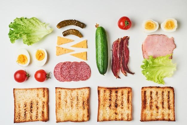 Sandwichbestandteile auf einem weißen hintergrund, draufsicht Premium Fotos