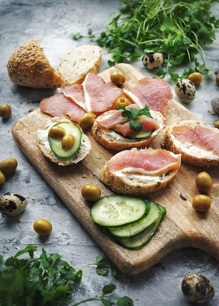 Sandwiche mit fleisch auf einem schneidebrett, lebensmittelzusammensetzung Premium Fotos