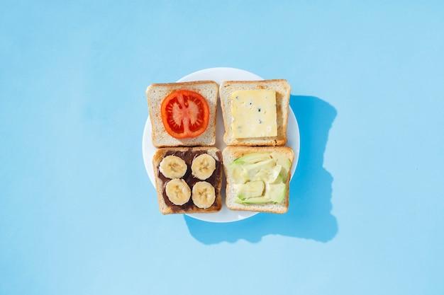 Sandwiche mit käse, tomate, banane und avocado auf einer weißen platte, blaue oberfläche. flachgelegt, draufsicht. Premium Fotos