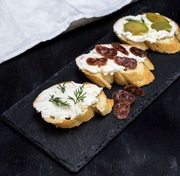 Sandwiches mit cremeweißkäse, wurst, oliven und dill Premium Fotos