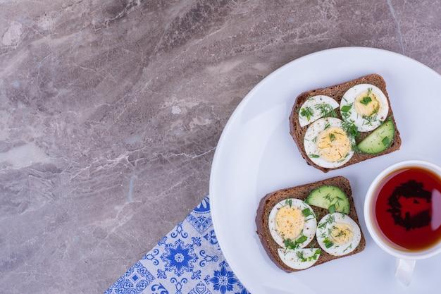 Sandwiches mit eiern und kräutern, serviert mit einer tasse tee Kostenlose Fotos
