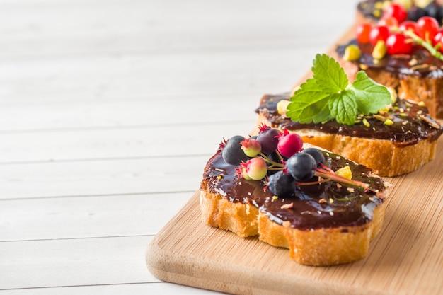 Sandwiches mit schokoladenpaste, pistazien und frischen beeren auf einem hölzernen umhüllungsbrett. platz kopieren Premium Fotos