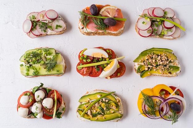 Sandwiches oder tapas mit brot, frischkäse, gemüse und leckeren belägen. Premium Fotos