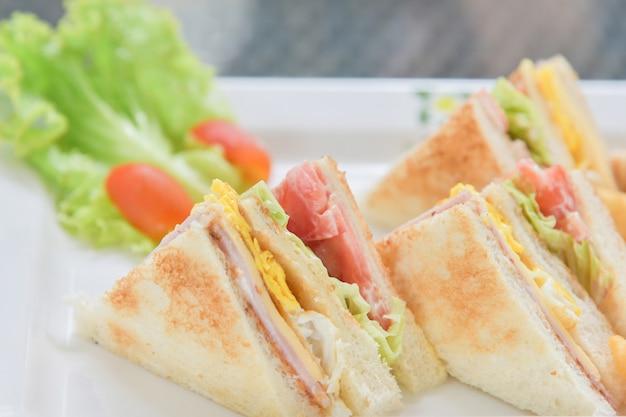 Sandwichfrühstück mit salat und tomate auf der weißen platte Premium Fotos