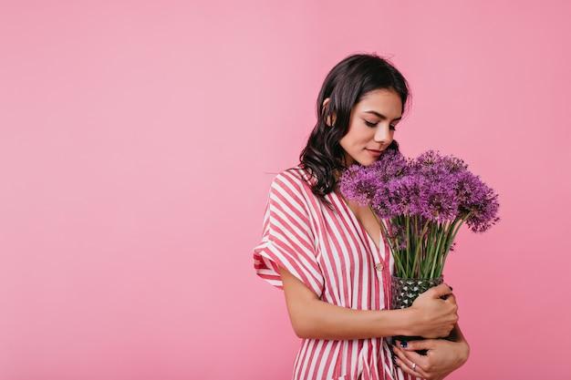 Sanfte junge frau in der romantischen stimmung ist niedlich, das arm voll blumen betrachtet. porträt der europäischen dame im stilvollen outfit. Kostenlose Fotos