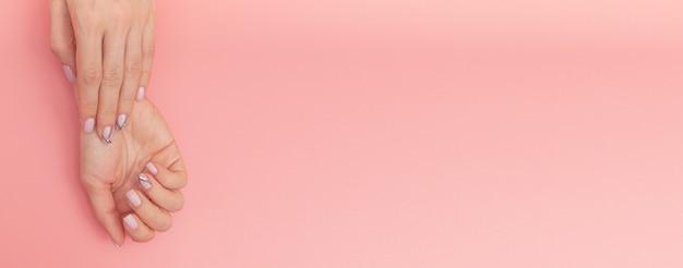 Sanfte nacktmaniküre. frauenhänden auf rosa Premium Fotos