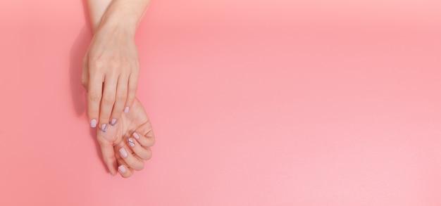 Sanfte nacktmaniküre. weibliche hände auf pastellrosa Premium Fotos
