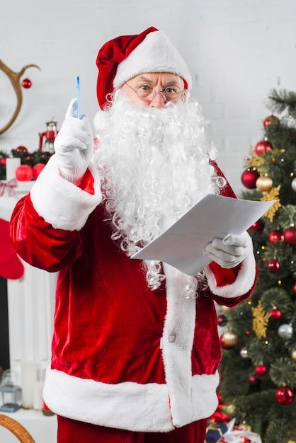 Sankt, die mit Papier nahe verziertem Weihnachtsbaum steht ...