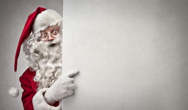 Santa claus, die auf ein brett zeigt Premium Fotos
