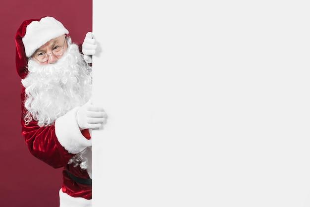 Santa claus, die aus weißer wand heraus schaut Kostenlose Fotos