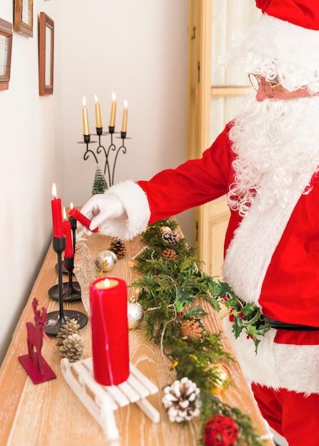 Santa claus, die beleuchtete kerze hält Kostenlose Fotos