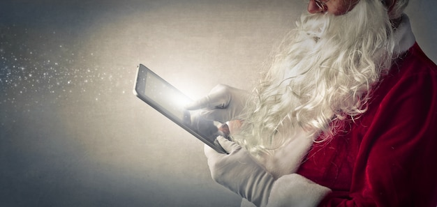 Santa claus, die eine tablette verwendet Premium Fotos