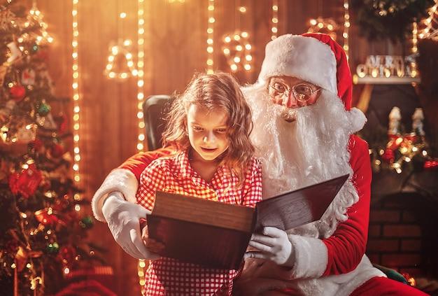 Santa claus, die einem kleinen netten mädchen ein geschenk gibt Premium Fotos