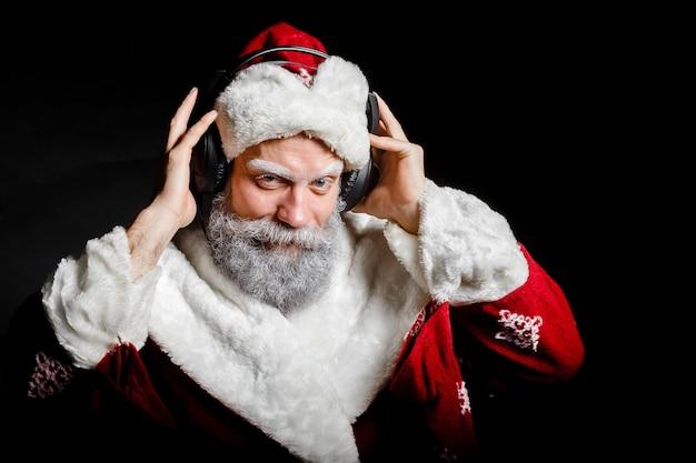 Santa claus hört musik mit kopfhörern auf einem schwarzen hintergrund Premium Fotos