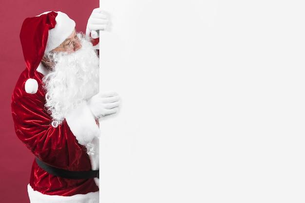 Santa claus in den gläsern, die aus weißer wand heraus schauen Premium Fotos