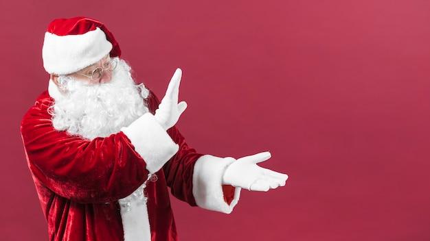 Santa claus in den gläsern, die etwas mit den händen zeigen Kostenlose Fotos