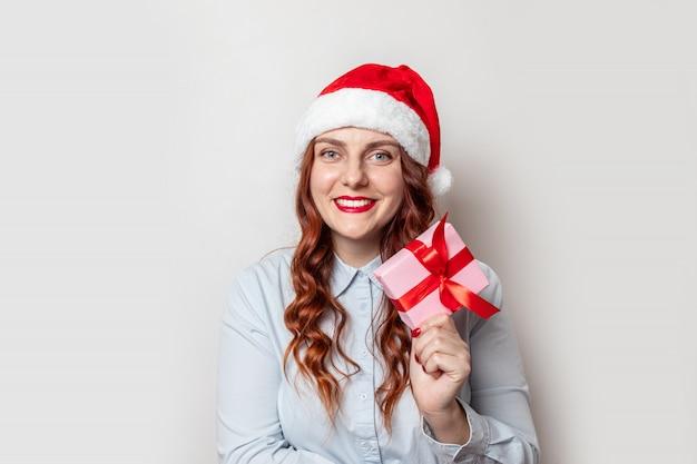 Santa claus-mädchen mit dem gelockten haar und einem roten hut mit einem bumbon hält eine geschenkbox mit einem roten satinbandbogen und lächelt auf einer grauen wand. frohe weihnachten und neujahr web-banner für die website. Premium Fotos