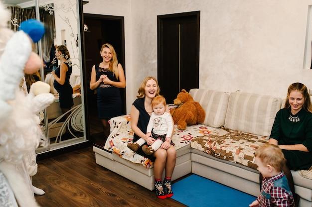 Santa claus und snow maiden brachten kindern geschenke. freudige kinder, die mit geschenken spielen. neujahrskonzept. fröhliche weihnachten. feiertags-, weihnachtsfamilien-, kindheits- und personenkonzept. Premium Fotos