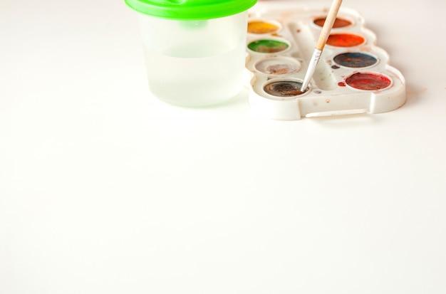 Satz aquarellfarben und pinsel zum malen auf weißer hintergrundnahaufnahme, kopienraum. selektiver fokus Premium Fotos