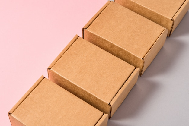 Satz braune pappkartons auf rosa und grauem hintergrund Premium Fotos