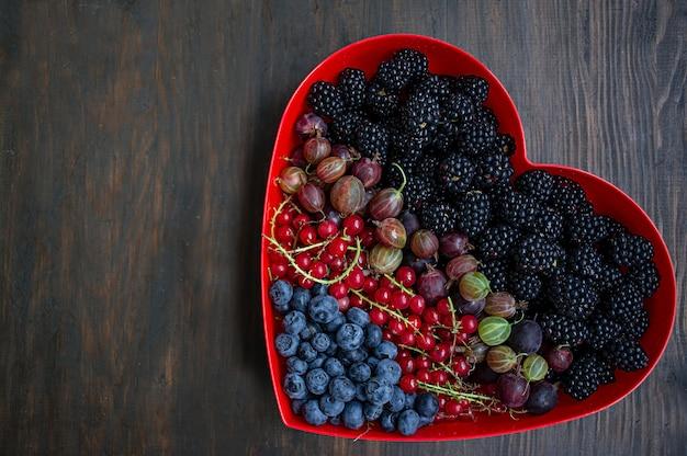 Satz brombeeren der frischen früchte, stachelbeeren, rote johannisbeeren, blaubeeren in einem roten herzkasten Premium Fotos