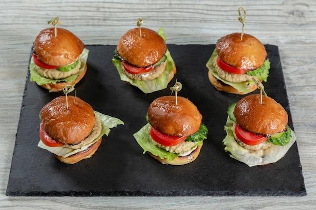 Satz burger auf schwarzem brett auf holztisch Premium Fotos