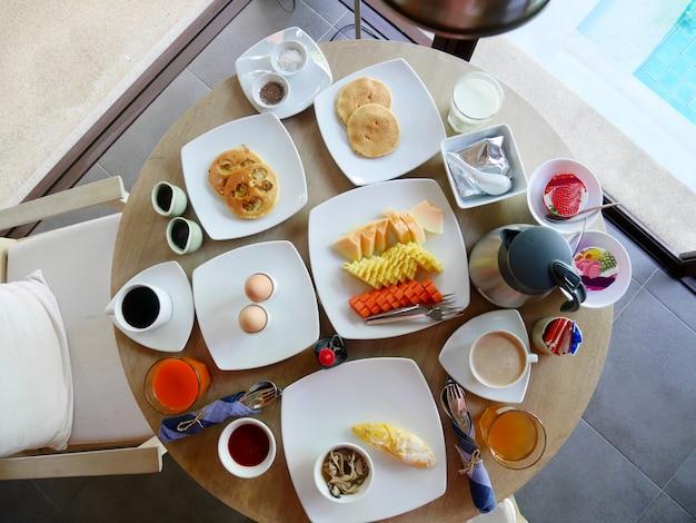 Satz des frühstücks auf dem runden holztisch morgens Premium Fotos