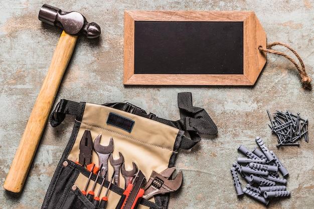Satz des handwerkzeugs mit nägeln und des kleinen tagschiefers auf schmutzhintergrund Kostenlose Fotos