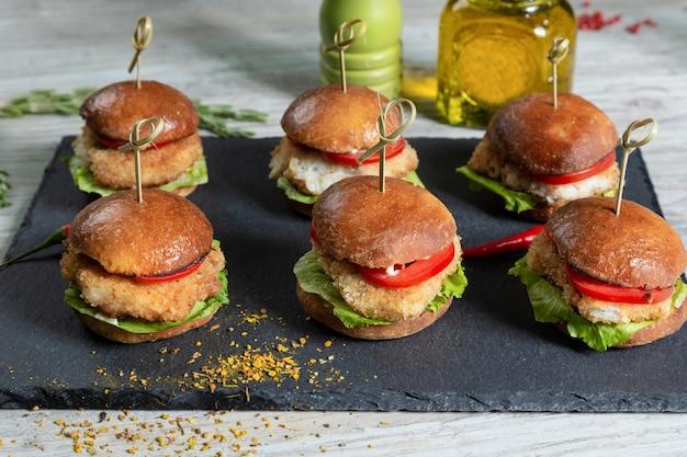 Satz fischburger auf schwarzem brett auf holztisch Premium Fotos