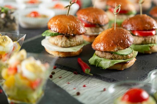 Satz fleischburger auf schwarzem brett auf holztisch Premium Fotos